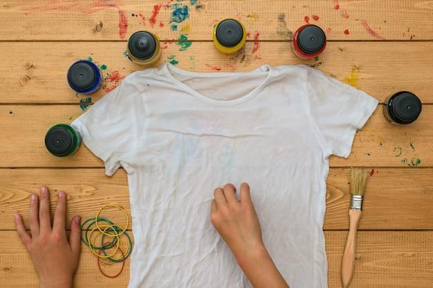Mädchen rollt ein weißes t-shirt für die anwendung der krawattenart auf. fleckiger stoff im tie-dye-stil.