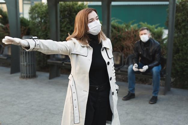 Mädchen ruft ein taxi an einer haltestelle während einer coronavirus-epidemie. covid 19.
