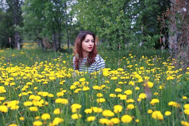 Mädchen ruht an einem sonnigen tag auf einer wiese mit gelbem löwenzahn