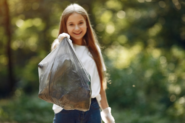 Mädchen sammelt müll in müllsäcken im park