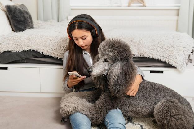 Mädchen schaut auf ihr handy, während sie auch ihren hund hält dog