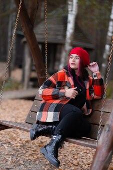 Mädchen schaut mit argwohn auf einer schaukel im herbst sitzend