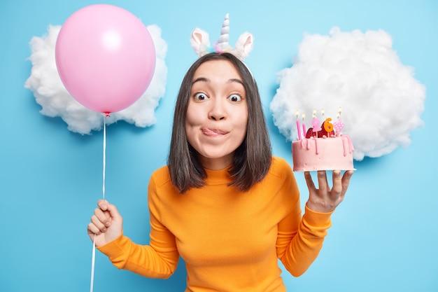 Mädchen schaut mit versuchung auf die kamera leckt die lippen will leckeren kuchen essen hat einen besonderen anlass feiert den 26. geburtstag hält aufgeblasenen ballon