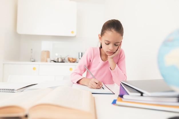 Mädchen schaut nachdenklich in das lehrbuch.