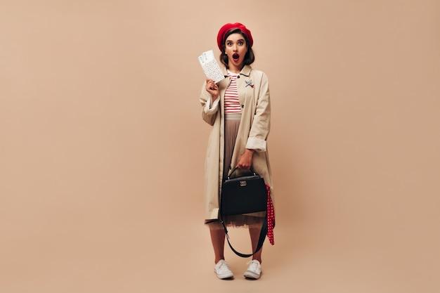 Mädchen schaut überrascht in die kamera und hält tickets. hübsche dame mit hellen lippen in roter baskenmütze, weißen turnschuhen und in beigen mantelposen.