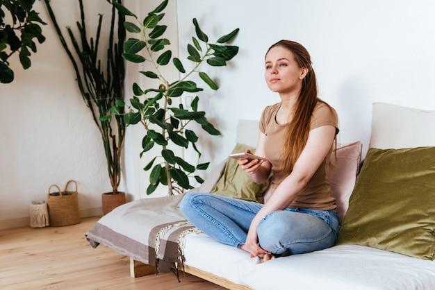 Mädchen schaut voraus, das auf dem sofa zu hause mit smartphone sitzt