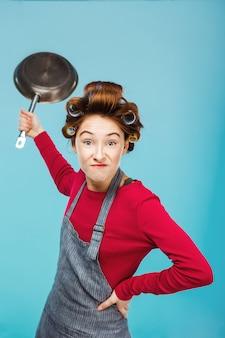 Mädchen scherzt mit bratpfanne in händen, während essen macht