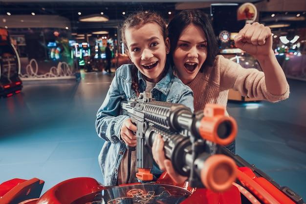 Mädchen schießt schwarze waffe in der spielhalle
