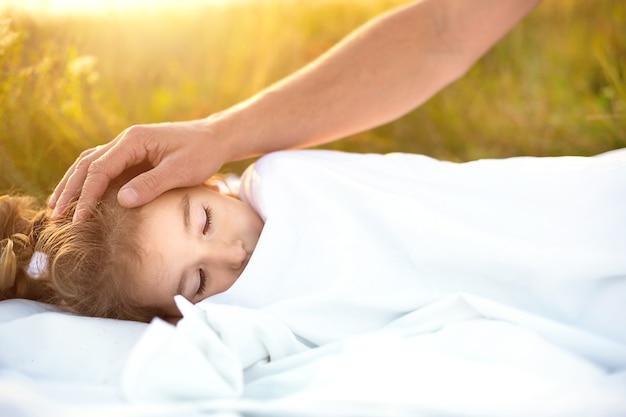 Mädchen schläft auf weißem bett im gras, frische luft und papas hand tätschelt sanft seinen kopf