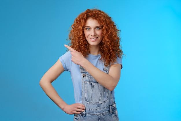 Mädchen schlagen perfekte platzanzeige vor. freche, gut aussehende, ermächtigte rothaarige, die mutige frau lächelt, die durchsetzungsfähig motiviert zeigt, die obere linke ecke grinsen zahnig zuversichtlich, dass sie promo-blauer hintergrund mögen.