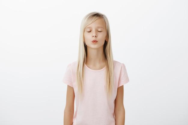 Mädchen schließt augen und erreicht lippen für kuss