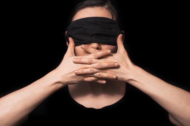 Mädchen schließt den mund mit den händen. brünette auf einem dunklen hintergrund. soziales foto, auf dem ein mädchen augen und mund schloss
