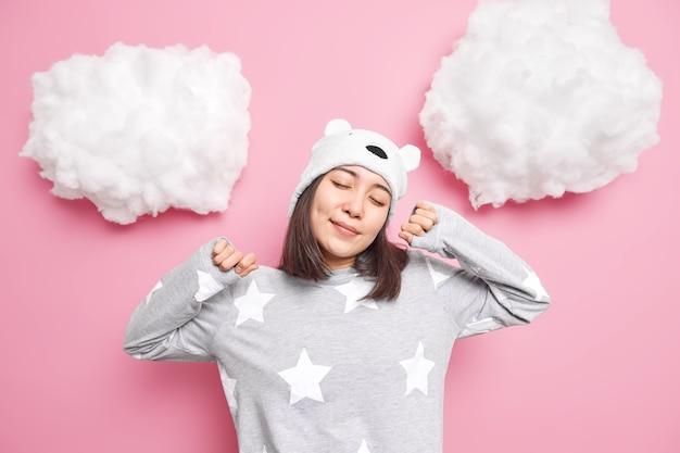 Mädchen schließt die augen und streckt sich morgens, trägt einen bequemen pyjama und der hut genießt die häusliche atmosphäre isoliert auf rosa