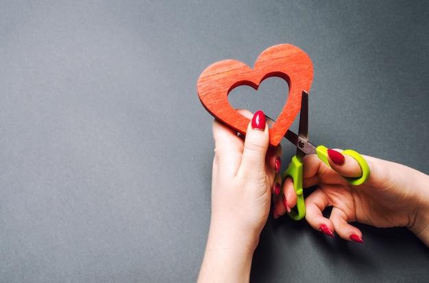 Mädchen schneidet das rote herz mit einer schere. das konzept des brechens von beziehungen, streitigkeiten und scheidungen.