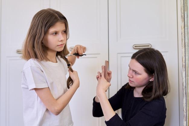 Mädchen schneidet ihre eigenen haare mit einer schere, ältere schwester teenager macht videos auf dem smartphone, für soziale netzwerke, blog, kanal Premium Fotos