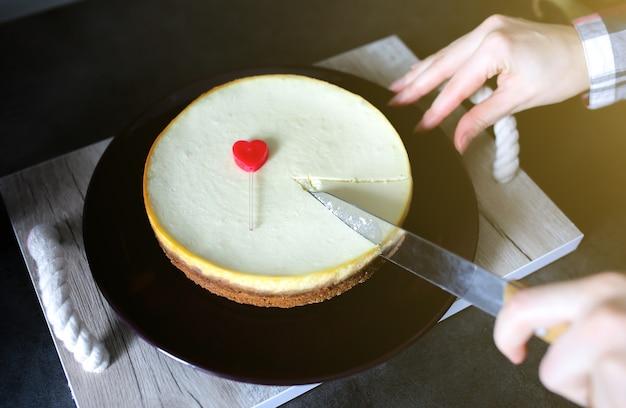 Mädchen schneidet mit einem messer klassischer vanille new yorker käsekuchen auf dunkelvioletter platte auf holztablett mit seilgriffen. kleines rotes herz liegt auf dem dessert. perfektes hygge-geschenk zum valentinstag.