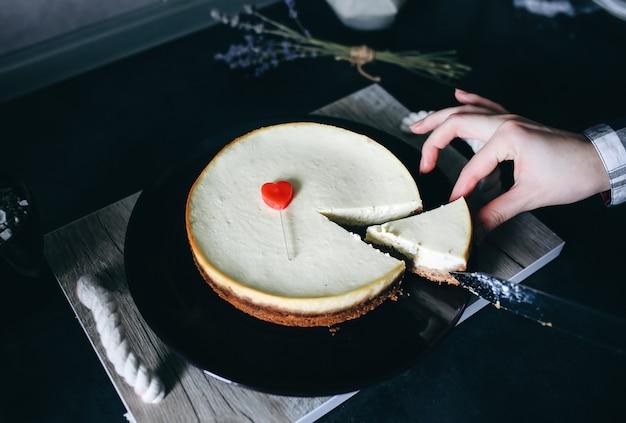 Mädchen schneidet mit klassischem vanille new yorker käsekuchen des messers auf dunkelvioletter platte auf holztablett mit seilgriffen. kleines rotes herz liegt auf dem dessert. perfektes hygge-geschenk zum valentinstag. hausgemacht.