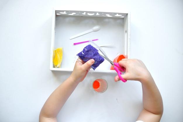 Mädchen schneidet mit schere kerzenstofftasche macht eine kerze aus kleinen paraffinkörnern