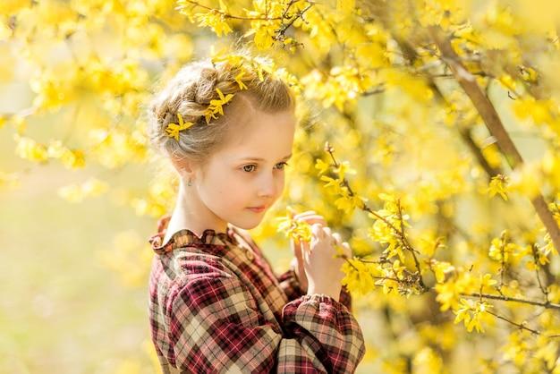 Mädchen schnüffelt gelbe blumen. ein kind vor dem hintergrund der forsythie. frühlingsporträt eines kindes mit blumen in ihren haaren