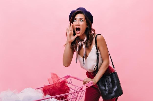 Mädchen schockiert durch rabatte beim einkaufen gesehen. dame in der schwarzen baskenmütze und mit der kleinen tasche hält rosa wagen auf lokalisiertem hintergrund.