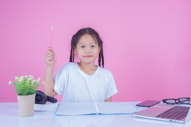 Mädchen schreiben bücher auf einem rosa hintergrund.
