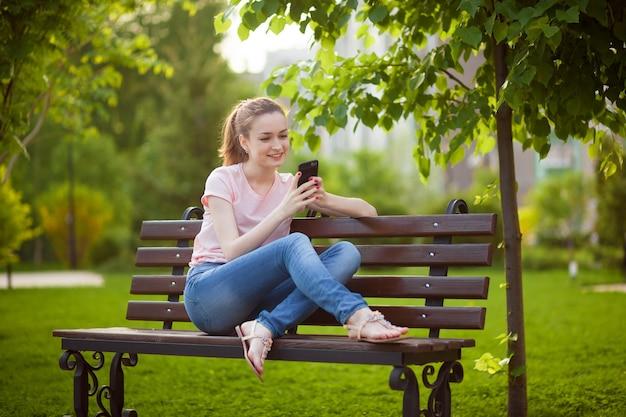 Mädchen schreibt am telefon, während es im park sitzt