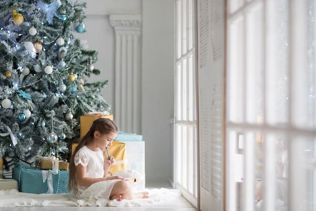 Mädchen schreibt brief an den weihnachtsmann in hellem raum mit weihnachtsbaum in den farben blau und gold