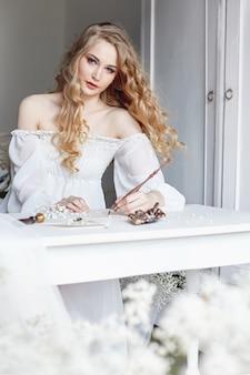 Mädchen schreibt einen brief an ihren geliebten mann, der in einem weißen lichtkleid, reinheit und unschuld zu hause am tisch sitzt. lockiger blonder romantischer look, schöne augen. weiße wildblumen auf dem tisch
