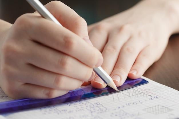 Mädchen schreibt in ein notizbuch mathematische formeln