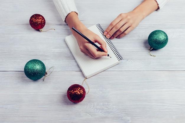 Mädchen schreibt in ein notizbuch mit einem bleistift, als nächstes auf dem tisch sind christbaumkugeln