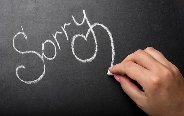 Mädchen schreibt mit weißer kreide die aufschrift sorry auf eine schwarze tafel mit einem platz für deinen text