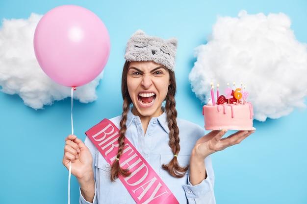 Mädchen schreit vor wut, hält köstlichen erdbeerkuchen und aufgeblasenen ballon, der wütend ist, weil die gäste nicht in häuslicher kleidung auf die party kamen, die gegen blau posiert