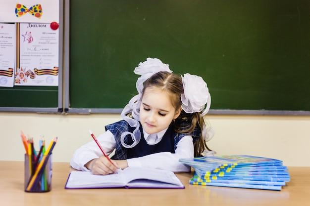 Mädchen schulmädchen und schule. das mädchen trägt in der schule eine schuluniform. ausbildung
