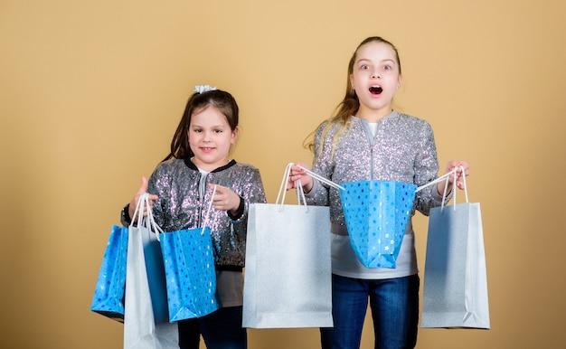 Mädchen schwestern freunde mit einkaufstaschen beige hintergrund. einkaufen und kaufen. schwarzer freitag. verkauf und rabatt. einkaufstag. kinder halten bündelpakete. kindermode. erwarte mehr. weniger bezahlen.