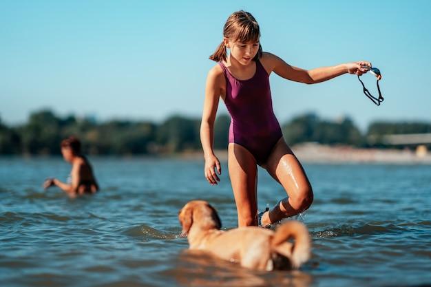 Mädchen schwimmen im fluss mit ihrem hund