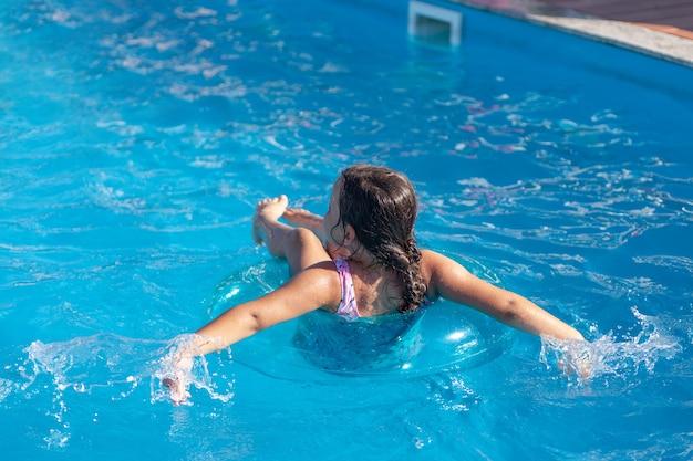Mädchen schwimmt auf einem aufblasbaren kreis im blauen wasser des pools des pools das konzept...