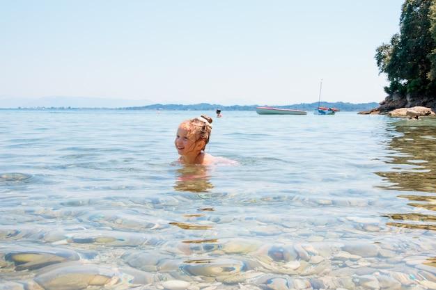 Mädchen schwimmt, hat spaß familiensommerferien. kinder schwimmen im meerwasser. wasserspaß