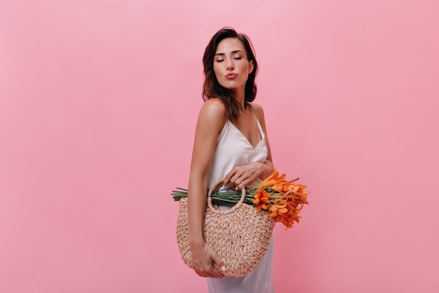 Mädchen sendet kuss und hält tasche mit blumen auf rosa hintergrund