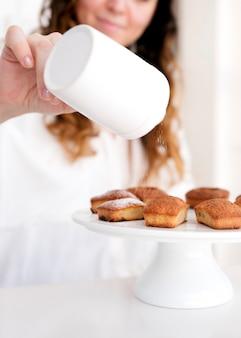 Mädchen serviert puderzucker auf muffin-top