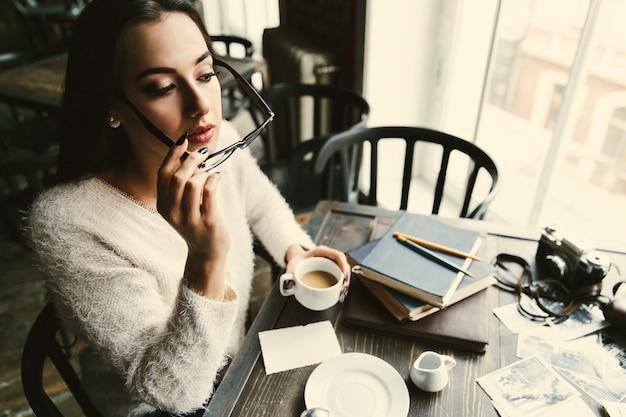 Mädchen setzt auf ihre gläser, die mit tasse kaffee im café sitzen