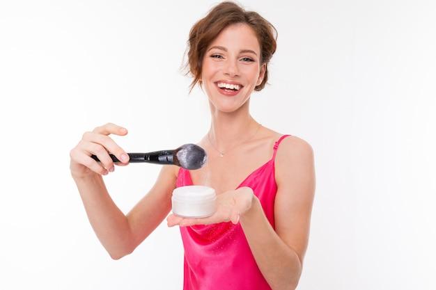 Mädchen setzt puder auf einen make-up-pinsel an einer weißen wand