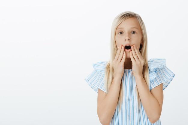 Mädchen sieht entzückende puppe im laden und bittet mutter, sie zu kaufen. porträt einer verblüfften und überraschten süßen blonden tochter, die den kiefer fallen lässt, wow sagt und hände in der nähe des geöffneten mundes über der grauen wand hält