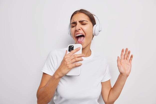 Mädchen singt lied hört musik in kopfhörern hält handy lässig gekleidet hat fröhlichen ausdruck auf weiß