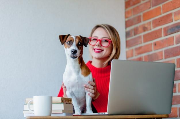 Mädchen sitzen am tisch mit computer und hund
