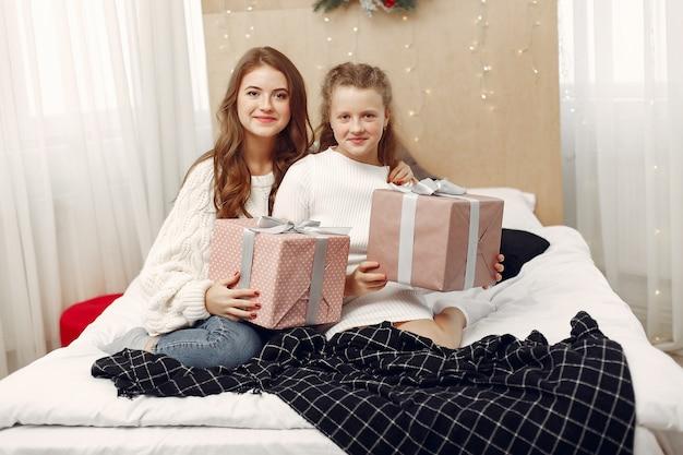 Mädchen sitzen auf dem bett. frauen mit geschenk. die schönheiten bereiten sich auf weihnachten vor