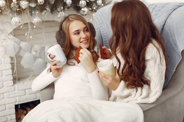 Mädchen sitzen auf dem stuhl. frauen mit tassen. schwestern bereiten sich auf weihnachten vor