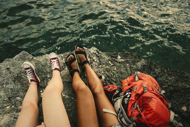 Mädchen sitzen auf einem felsen am meer
