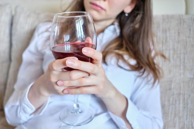 Mädchen sitzen auf einem sofa und trinken wein.