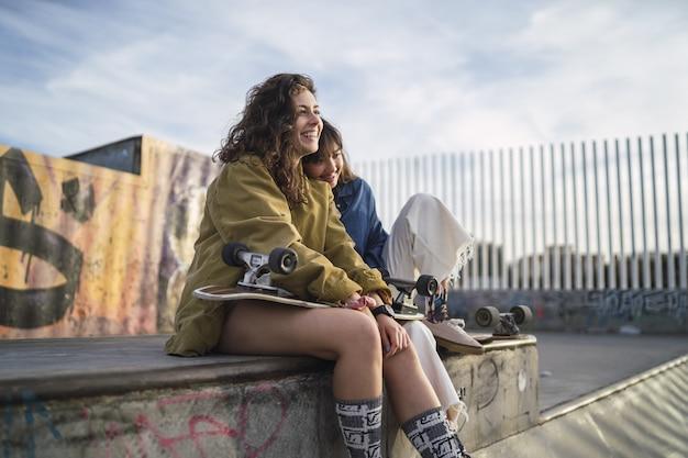 Mädchen sitzen dicht nebeneinander in einem park