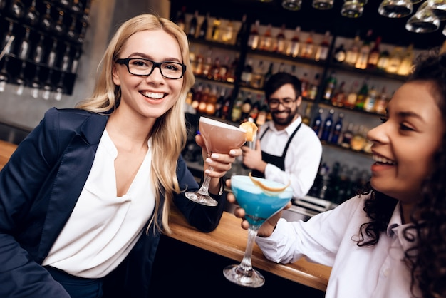 Mädchen sitzen mit cocktails an der bar.